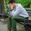 Troubled young man sitting in the park — Stock Photo #45553221