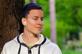 Young man listening to the music in the park — Foto de Stock