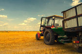 Modern red tractor on the agricultural field  — Stock Photo