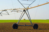 Irrigation system and combine harvesting green peas — Stock Photo