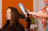 Hairdresser making hair of beautiful girl — Stock Photo
