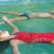 Little boy and litlle girl floating on the water surface of the — Stock Photo #49903113