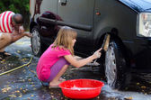 Happy daughter helping father to wash car — Stockfoto