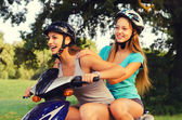 Two happy teenage girlfriends riding scooter — Stockfoto