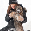 Pretty teenage girl plays with her dog in thick snow — Stock Photo #9097596