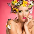 Stock Photo: Beautiful woman with flowers and butterflies