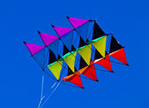 A rainbow colored kite against a blue sky — 图库照片