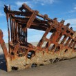 Stock Photo: Rusty Wreckage of Ship on Beach