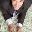 Smiling businessman lying on money — Foto Stock