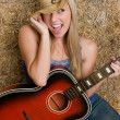 Blonde cowgirl holding guitar — Stock Photo