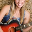 Blonde cowgirl playing guitar — Stock Photo