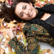 Royalty-Free Stock Photo: Woman lying on autumn leaves background
