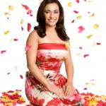 Portrait of brunette on rose petals background — Stock Photo