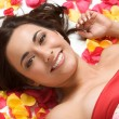 Charming lady lying on rose petals background — Stock Photo #21821661