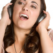图库照片: Girl listening music in headphones and singing