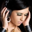 Girl listening music in headphones — Stockfoto
