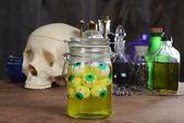 Jar of eyeballs skull and potions — Stock Photo