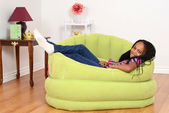 South African child relaxing in green chair — Stock Photo