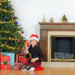 Child shaking christmas present by tree - Zdjęcie stockowe