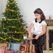 Stock Photo: Little girl putting out cookies milk for santa