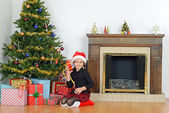 Child shaking christmas present by tree — Stock fotografie