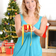 Blonde woman giving christmas present — Stock Photo #16313315