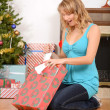 Blonde woman opening christmas present — Stock Photo