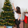 Child hanging candy cane on christmas tree - Foto Stock