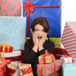 Child surprised with lots of christmas gifts — Stock Photo
