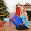 Young woman with blue christmas present - Stockfoto