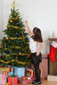 Child hanging candy cane on christmas tree — Stock Photo