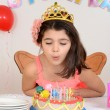 Foto Stock: Young girl blowing birthday candles