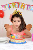 Young girl blowing birthday candles — Stock Photo