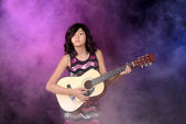 Young girl playing guitar on stage — Stock Photo