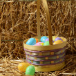 Closeup Easter eggs with basket and straw — Stock Photo
