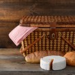 Picnic basket with bread and cheese on wood — Stock Photo