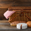 Picnic basket with bread and cheese on wood - Stock Photo