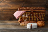 Old picnic basket with wine and cheese — Stock Photo