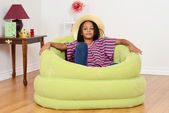 Black child relaxing in green chair — Stock Photo