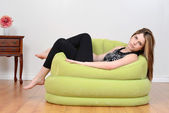 Teen relaxing in green bean bag chair — Zdjęcie stockowe