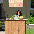 Bored girl at lemonade stand — Stock Photo