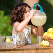Little girl drinking from lemonade pitcher — Stockfoto
