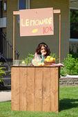 Bored girl at lemonade stand — Stock Photo