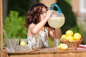 Little girl drinking from lemonade pitcher — Stock Photo