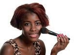 Young black woman putting on blush makeup — Stock Photo