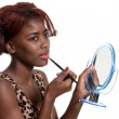 Black woman putting on pink lip gloss — Stock Photo