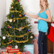 Blonde woman hanging christmas ornament on tree — Stock Photo