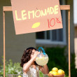 Girl drinking lemonade from a pitcher — Photo