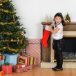 Surprised little girl with christmas stocking — Stockfoto