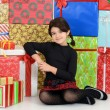 Young child leaning on christmas presents — Stok fotoğraf